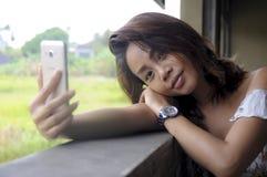 拍与手机照相机微笑的愉快坐的年轻美丽的亚裔女孩selfie照片户外在咖啡店 免版税图库摄影