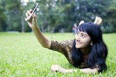 拍与手机的亚裔妇女照片在公园 库存照片