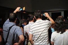 拍与手机的人们照片 免版税库存图片