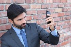 拍与手机的商人selfie照片 免版税库存图片