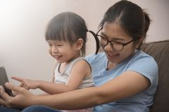 拍与手机的女儿和年轻母亲照片 免版税库存照片