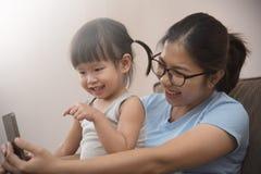 拍与手机的女儿和年轻母亲照片 免版税库存图片