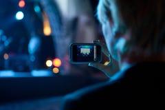 拍与手机的女商人照片在音乐会 免版税库存照片