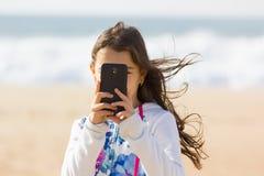 拍与手机的女孩照片在海滩 免版税库存照片