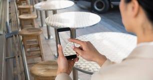 拍与手机的女实业家照片在咖啡店 库存图片