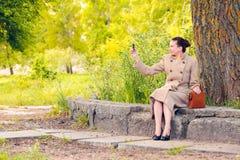 拍与手机的妇女一张照片 免版税库存图片