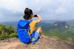拍与手机的妇女远足者照片远足在山峰 免版税库存图片