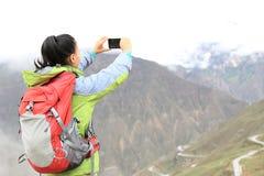 拍与手机的妇女远足者照片 免版税库存图片