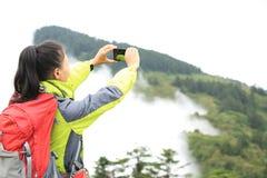 拍与手机的妇女远足者照片 库存照片