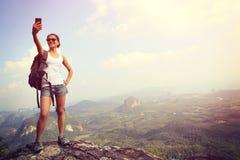 拍与手机的妇女远足者照片 免版税库存照片