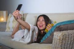 拍与手机的年轻美丽和愉快的亚裔中国人20s或30s妇女selfie照片在家喝橙汁liv 免版税库存照片
