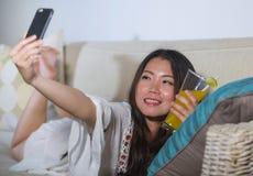 拍与手机的年轻美丽和愉快的亚裔中国人20s或30s妇女selfie照片在家喝橙汁liv 免版税图库摄影