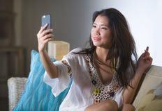 拍与手机的年轻美丽和愉快的亚裔中国人20s或30s妇女selfie照片在家坐客厅沙发 免版税库存照片
