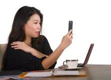 拍与手机的愉快的亚裔中国女商人selfie照片在公司公司办公桌微笑嬉戏在femal 免版税库存照片