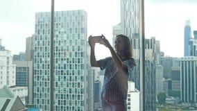 拍与手机的愉快的深色的俏丽的妇女selfie照片由窗口在公寓有美好的都市看法 图库摄影