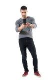 拍与手机的时髦年轻人照片佩带红色运动鞋 免版税库存照片