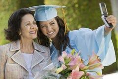 拍与手机的毕业生和祖母照片 免版税库存图片