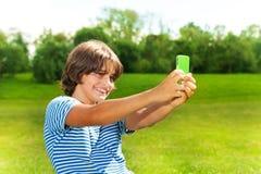 拍与手机的男孩照片 库存图片