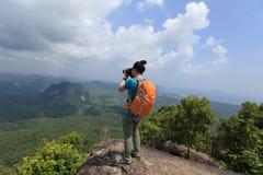 拍与手机的远足者照片远足在山峰 图库摄影