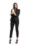 拍与手机的黑衣服的愉快的女商人照片 免版税库存图片