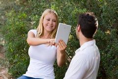 拍与数字式片剂的白肤金发的女孩照片 免版税图库摄影