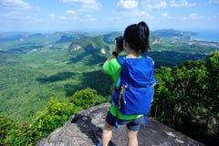 拍与数字照相机的背包徒步旅行者照片在山峰 库存照片