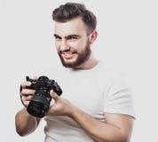 拍与数字照相机的年轻有胡子的摄影师照片 库存照片