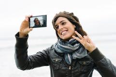 拍与智能手机和微笑的偶然妇女selfie照片 免版税库存照片