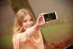 拍与智能手机照相机的女孩自已照片户外 库存照片