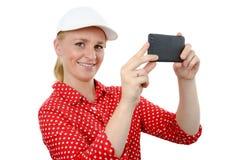 拍与智能手机照相机的微笑的妇女照片,在白色 免版税图库摄影