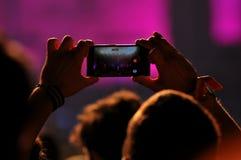 拍与智能手机的人人群照片在音乐会 库存图片