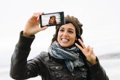 拍与智能手机的偶然妇女selfie照片 免版税库存照片