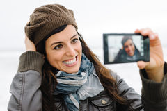 拍与智能手机的偶然愉快的妇女selfie照片 库存图片