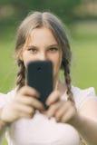 拍与智能手机的十几岁的女孩照片 库存照片