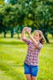 拍与智能手机的可爱的十几岁的女孩照片在晴天 库存照片