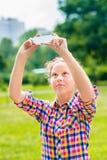 拍与智能手机的可爱的十几岁的女孩照片在晴天 免版税图库摄影