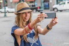 拍与智能手机的女孩照片 免版税库存图片