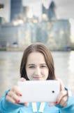 拍与智能手机的妇女一张照片 库存照片