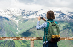 拍与智能手机的妇女远足者照片在山 背包徒步旅行者在手机的照片风景 免版税图库摄影