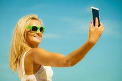 拍与智能手机的愉快的女孩自已照片 库存照片