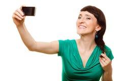 拍与智能手机的愉快的妇女自已照片 免版税库存照片