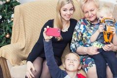 拍与智能手机的愉快的家庭照片在Chistmas装饰 库存照片