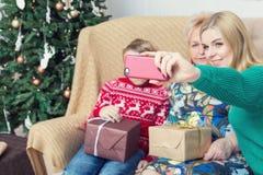 拍与智能手机的愉快的家庭照片在Chistmas装饰 库存图片