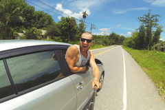 拍与智能手机的年轻愉快的人Selfie照片在Monopod棍子 做旅行照片的行家由车窗 图库摄影