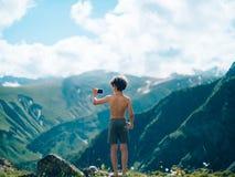 拍与智能手机的年轻男孩照片在山 免版税库存图片