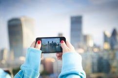 拍与智能手机的WomanÂ的手一张照片 免版税库存照片