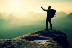 拍与智能手机,山峰的坚强的远足者照片 库存图片