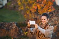 拍与机动性的妇女照片,当放松在秋天公园时 库存照片