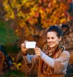 拍与机动性的妇女照片,当放松在秋天公园时 免版税图库摄影