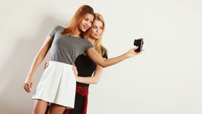 拍与照相机的两个模型女孩自已照片 免版税库存照片